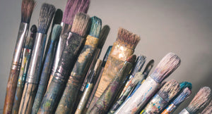 Paint brushes used in an art studio. Photo by Laura Adai on Unsplash