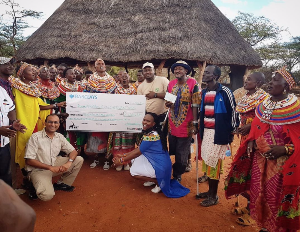The BeadWORKS artisans of Kalama Conservancy present their conservation  contribution check for 2018 to their chairperson during a ceremony in  late May.