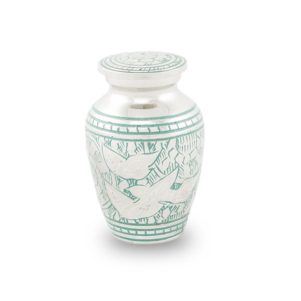 Keepsake urn is nickel plated brass with blue paint filling. Handcarved leafy design with 3 doves.
