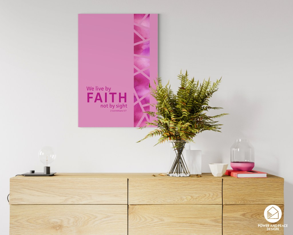 Pink Scripture art with 2 Corinthians 5:7 hanging on the wall above a wooden credenza.