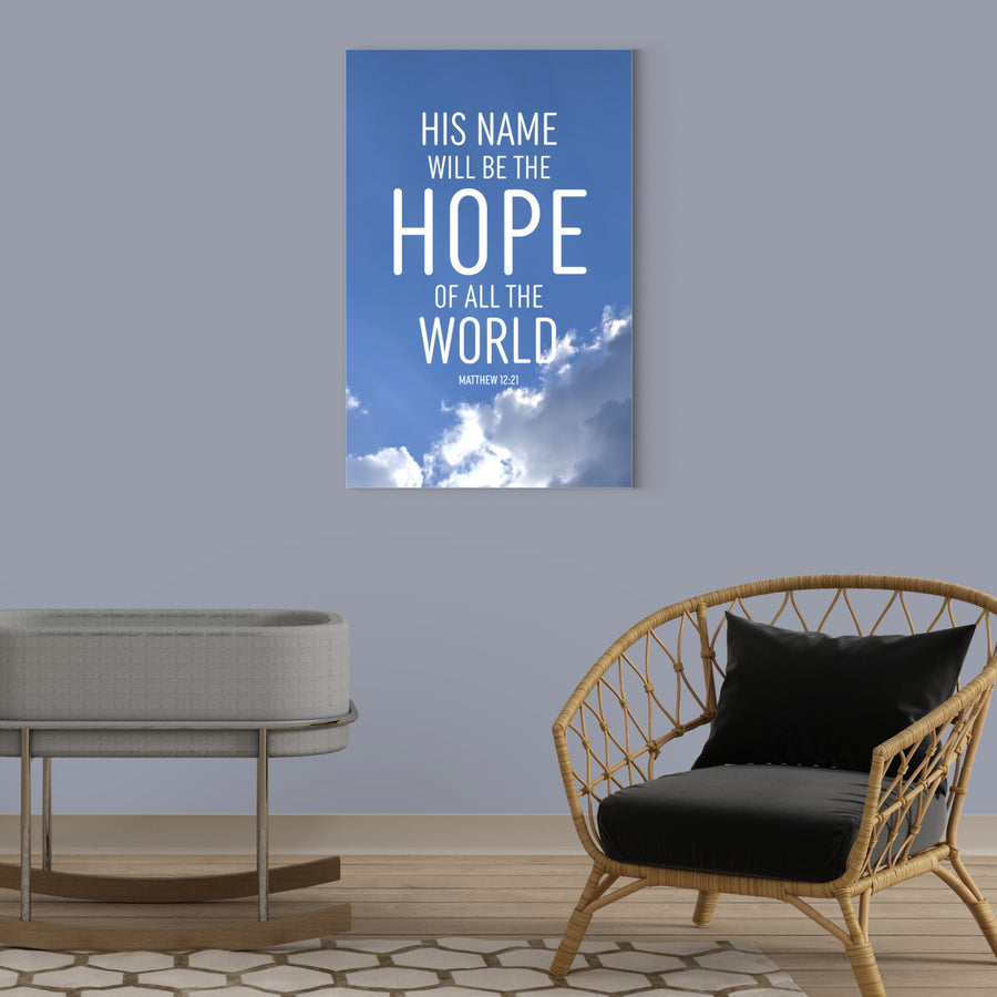 Nursery with blue-gray walls, a gray bassinet, and a wicker chair with black cushions. Large Christian canvas with the words His name will be the hope of all the world. Matthew 12:21. The background of the art is a photograph of the sky with fluffy white clouds lit by the sunshine.