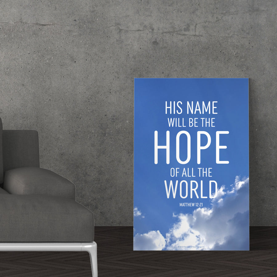 Bible verse canvas leaning against a gray cement wall near a gray couch. Canvas has a photograph of the blue sky with fluffy white clouds on the bottom. Text reads: His name will be the hope of all the world. Matthew 12:21.