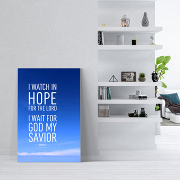 Blue Christian canvas leaning against a white wall near a shelf in a living room scene. Text on canvas reads: I watch in hope for the Lord. I wait for God my Savior. Micah 7:7.