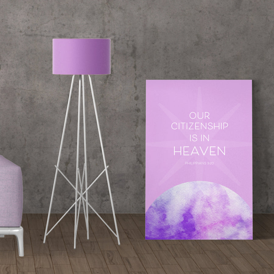 Large lavender Christian canvas with Philippians 3:20: Our citizenship is in heaven. Canvas is shown leaning against gray wall, dark wood floors, lamp to the left.