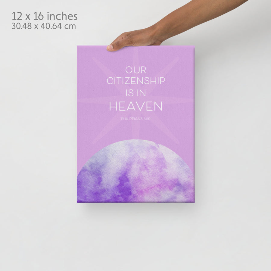 Lavender Bible verse canvas held by a hand extending from top of image. Canvas design has the words Our citizenship is in heaven. Philippians 3:20. Label in corner reads 12x16 inches.