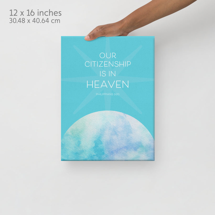 Hand extending from top of image holding Scripture canvas. Label in corner reads 12x16 inches. Canvas is teal with watercolor planet on the bottom. Text on the top half is white and reads Our citizenship is in heaven. Philippians 3:20.