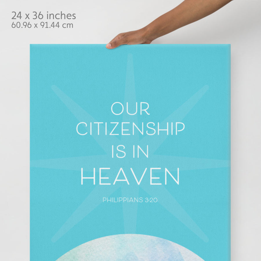 Hand extending from top of image holding Bible canvas. Label in corner reads 24x36 inches. Canvas is teal with watercolor planet on the bottom. Text on the top half is white and reads Our citizenship is in heaven. Philippians 3:20.