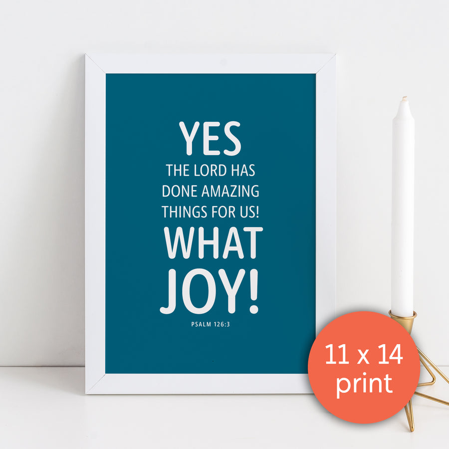 Framed Scripture art print. Bible verse art has peacock blue background with white text in rounded typeface reading Yes the Lord has done amazing things for us! What joy! Psalm 126:3. White candlestick in bronze holder to the right of framed image. Coral circle in lower right corner labels art as 11x14 print.