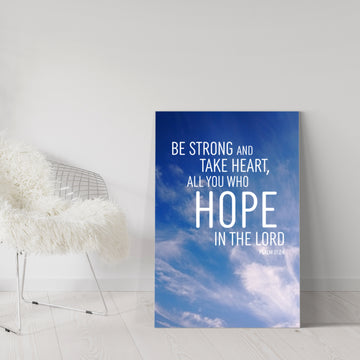 Large blue Christian canvas leaning against white wall in room with white floors. Silver chair with furry white throw to the side. Text on canvas reads: Be strong and take heart, all you who hope in the Lord. Psalm 31:24.