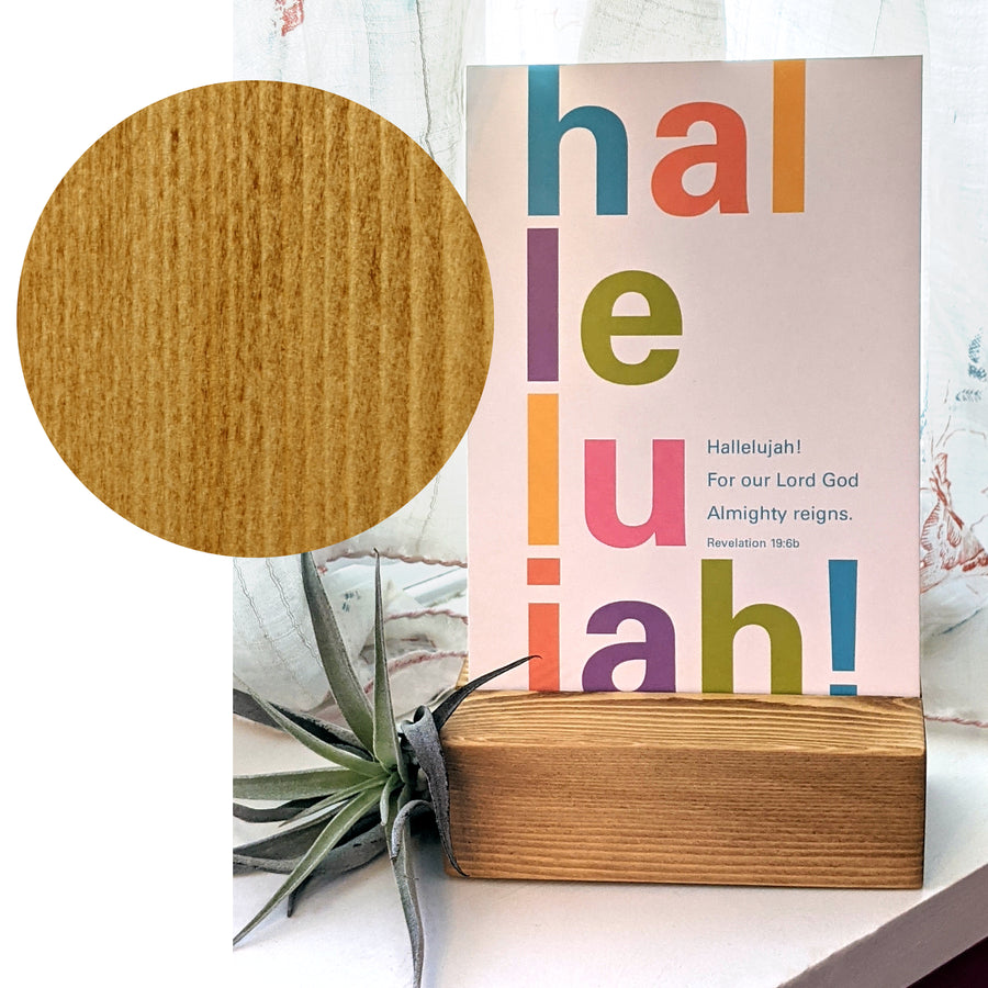 Large circle showing wood grain overlaps a photograph showing a white Bible verse postcard displayed in a wood block on a windowsill. Large colorful letters read Hallelujah! Smaller text reads Hallelujah! For our Lord God Almighty reigns. Revelation 19:6b.