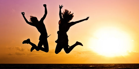 Two girls jumping in the sunset