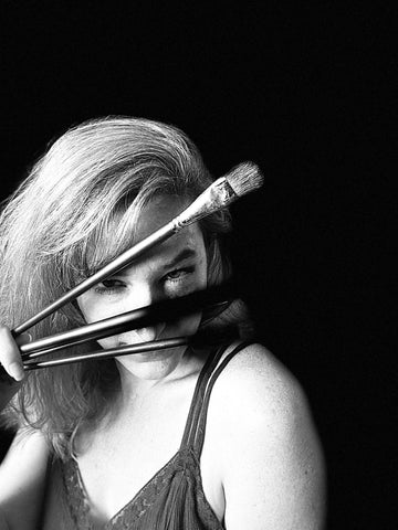 Black and white photo of artist, Cassidy Austin, with paint brushes