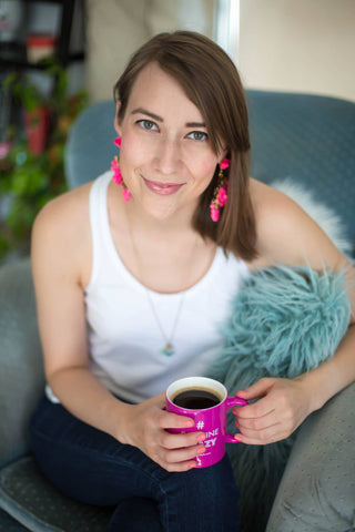 Author Natalie Wise on a couch with a cup of coffee in her studio