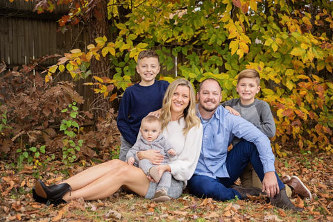 Cody-and-family-sitting-on-ground-with-fall-leaves-in-background-family-portrait