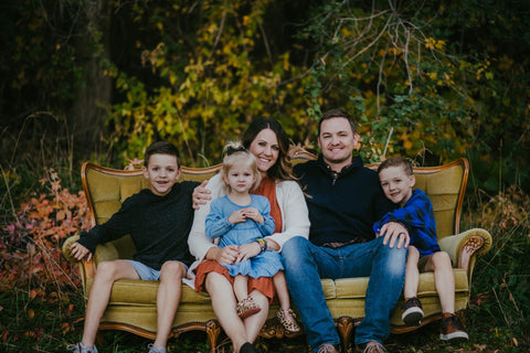 Matt-and-family-sitting-on-rustic-couch-with-fall-trees-in-background-family-portrait