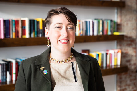 Photo of Posh&Page's founder, Mandy Shunnarah. She's a white woman with short brown hair. She's standing in front of a bookshelf wearing a green blazer, striped shirt, and gold jewelry, all of which are vintage.
