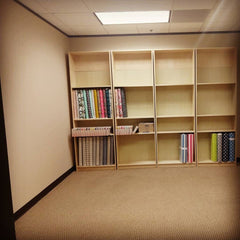 Room with sparing shelves and fabric.