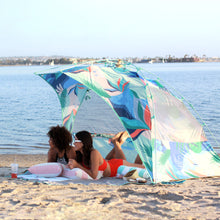 Load image into Gallery viewer, Two women comfortably lounge on blankets and pillows in the shelter on a beach.