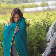 Load image into Gallery viewer, Woman smiling outside with the camp quilt wrapped around her.