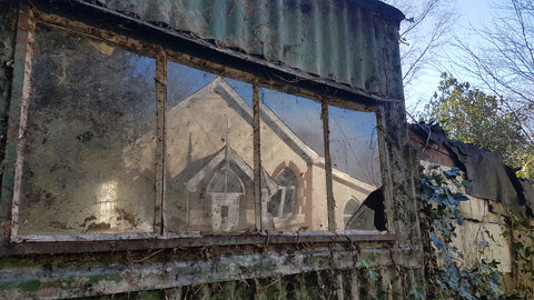 Chapel reflection in old potting shed window