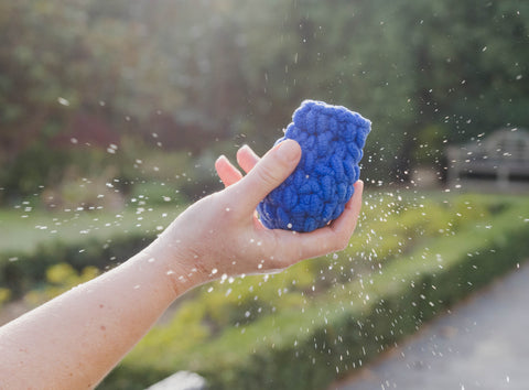 EcoSplat reusable water balloon in hand with water in the garden