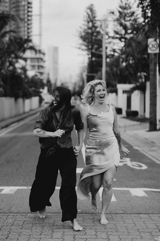 Katie and Heaven the creators of bare bouquets running down the street on their wedding day