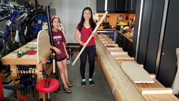 Two young canoebuilders stand beside their materials in a woodshop