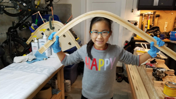 A young canoe builder poses with the wood bent stems of a canoe