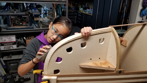 A young canoe builder sands the stems of a early canoe build