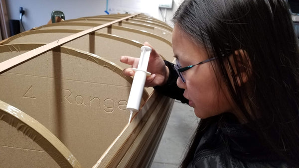 A young canoe builder glues cedar strips during the strip planking process