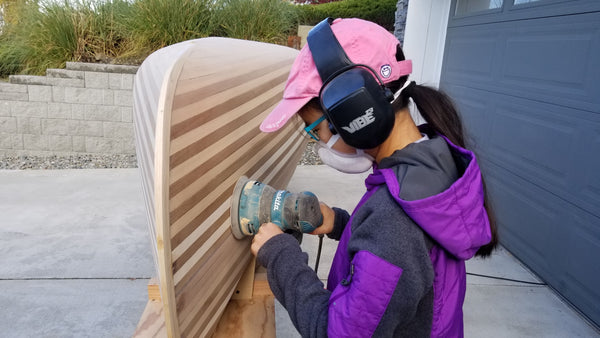 A young canoe builder sands the hull of a cedar strip canoe
