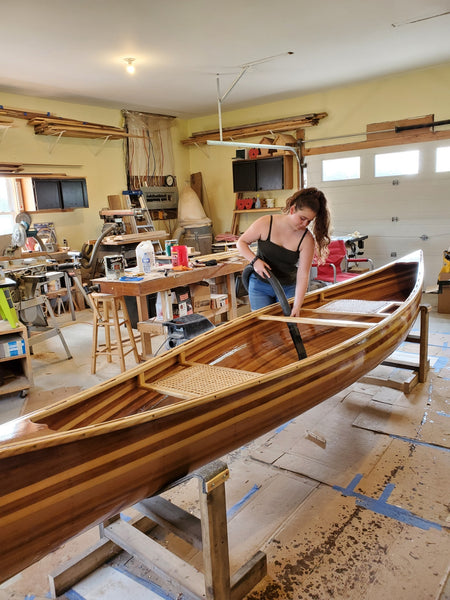 A young woman vacuums the inside of a canoe