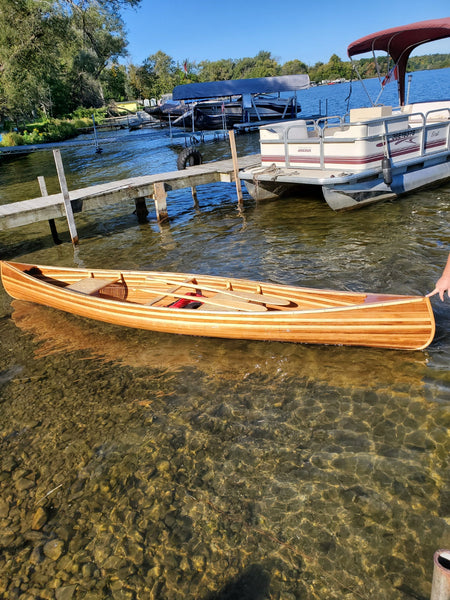A completed Bob's Special wooden canoe floats in shallow water