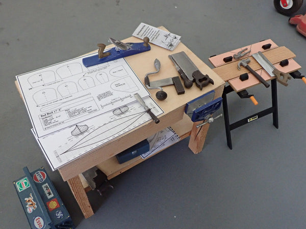 A scale model workbench with mock canoe plans and hand tools on it