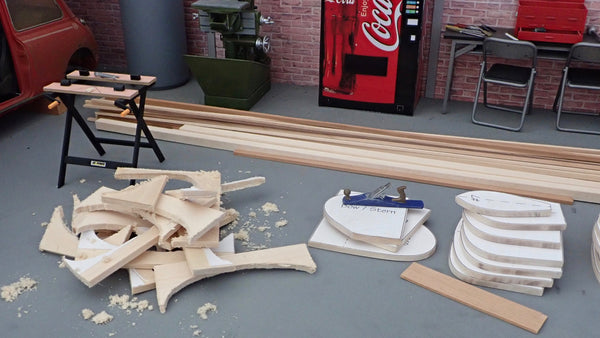A scale model strongback for canoe building with canoe molds beside it