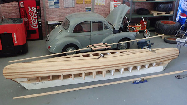 Overhead view of partially planked scale model canoe and model car