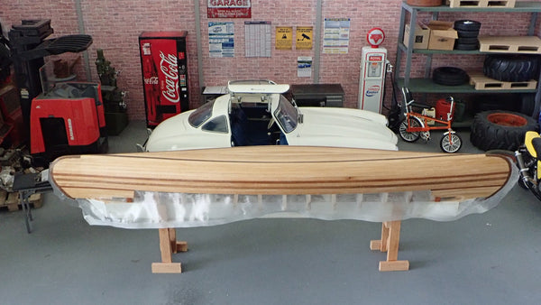A scale model canoe in the fibreglassing stage with a scale model car behind it