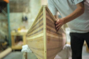 A man checks inside a nearly finished wooden canoe