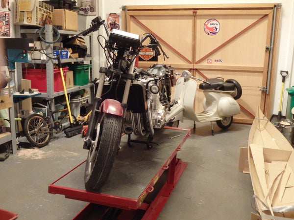 A scale model motorcycle sits in a diorama garage