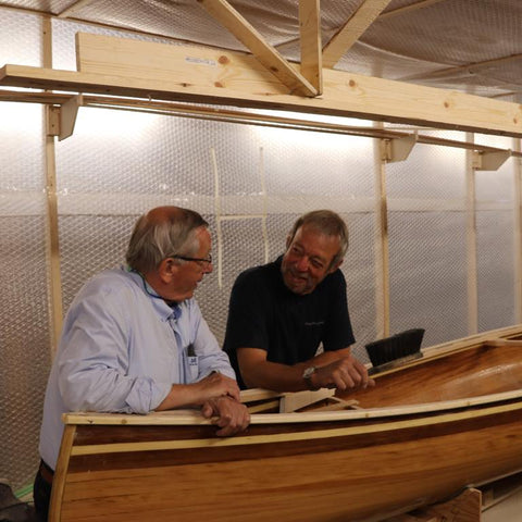 Two canoe builders chat during a stapleless canoe building workshop
