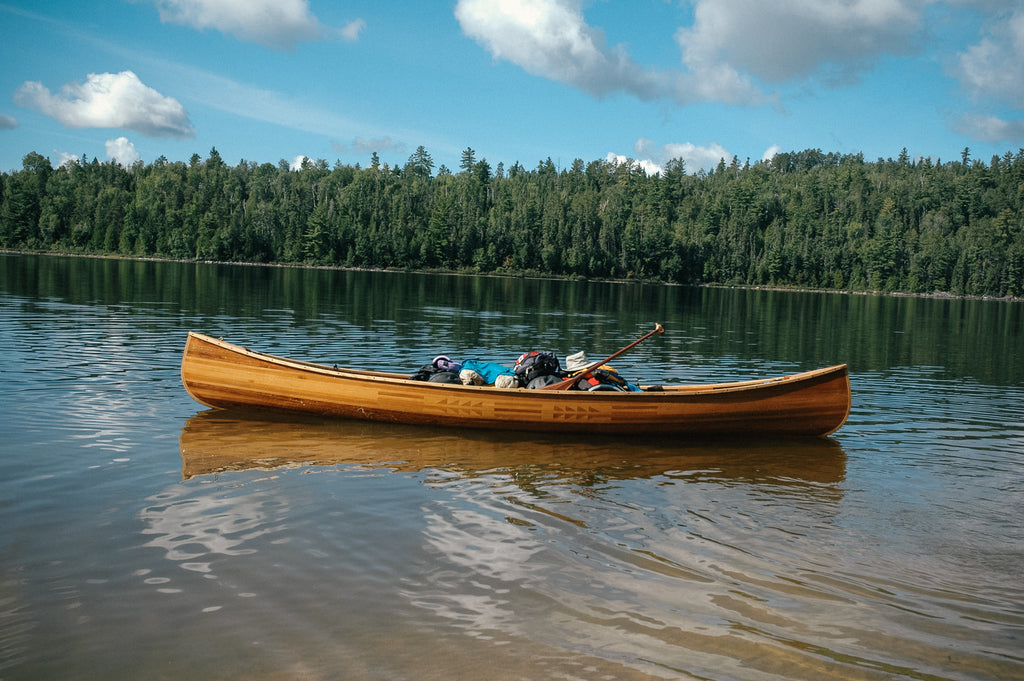 A wooden full of gear floats in a calm lake
