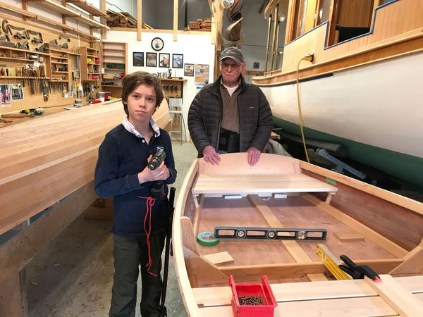 Ted Moores and grandson stand beside a partially completed plywood boat