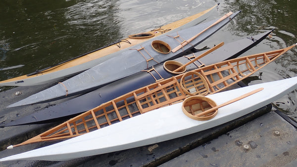 A collection of five scale model kayaks arrayed beside the water
