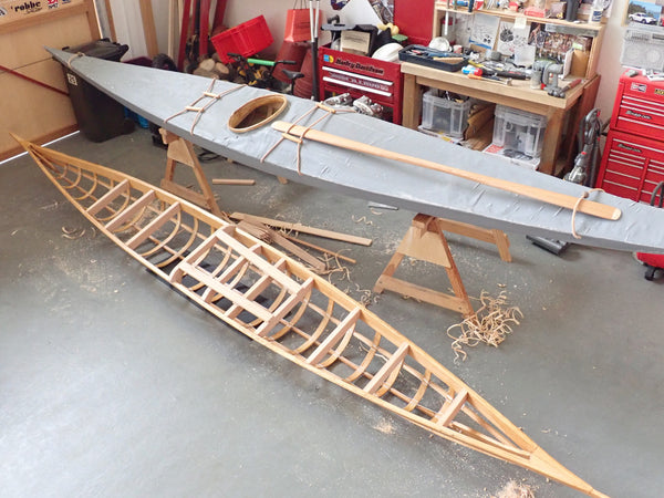 One finished and one partially complete Greenland kayak scale model, in a diorama workshop