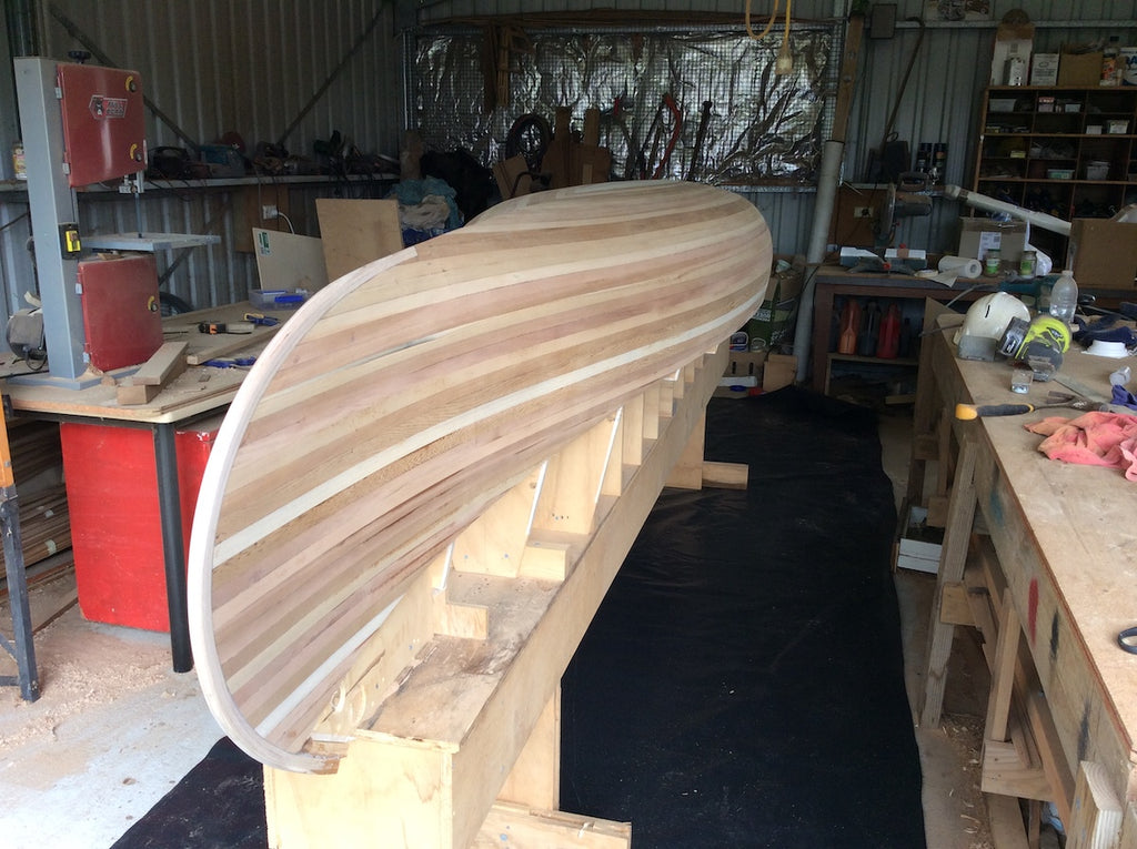 A sanded wooden canoe hull, unfibreglassed and sitting on the strongback