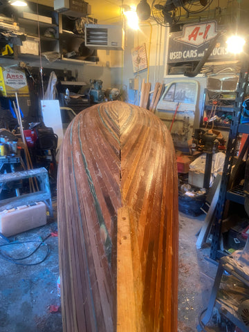 A fully planked but unfinished canoe hull in a workshop