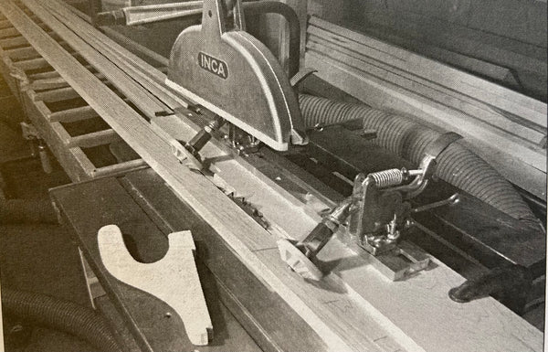 Photo shows anti-kickback jig in use, holding a plank down on a table saw