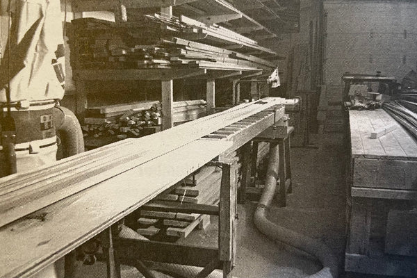 Long, level low-friction surface set up in a woodshop as outfeed for cutting planking