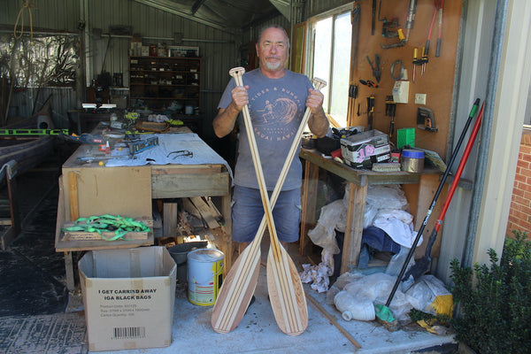 Keith stands in his workshop with two crossed wooden paddles