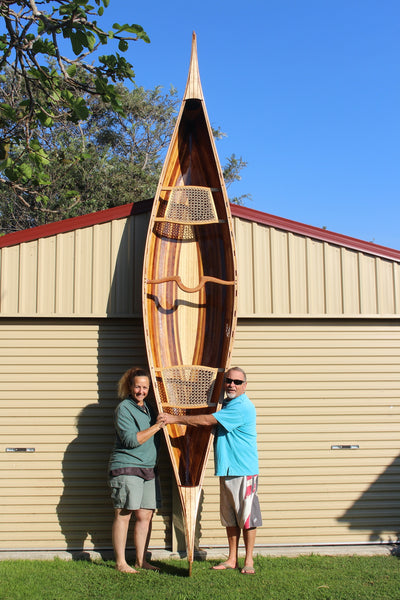 Keith and Nicki stand with finished Champlain canoe upright against a garage